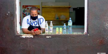 Un dependiente con mascarilla revisa su teléfono móvil tras la flexibilización de las restricciones por la COVID-19 en La Habana. Foto: Otmaro Rodríguez.