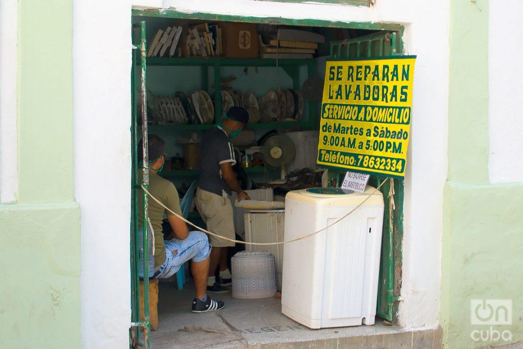 Trabajadores en un taller privado de reparaciones de lavadoras, tras la flexibilización de las restricciones por la COVID-19 en La Habana. Foto: Otmaro Rodríguez.