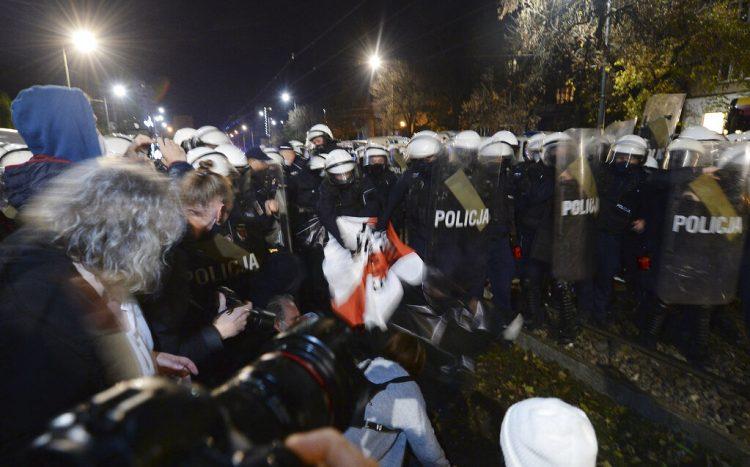 La policía arranca un cartel mientras manifestantes se concentran frente a la residencia del dirigente oficialista polaco Jaroslaw Kaczynski para protestar un fallo de la Corte Constitucional que endurece las leyes contra el aborto.  Foto: Czarek Sokolowski/AP.
