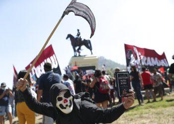 Un manifestante con una máscara sostiene la constitución de Chile mientras se manifiesta durante el primer aniversario del inicio de las protestas masivas contra el gobierno desencadenadas por el aumento de la tarifa del metro, que llevó a demandas por un cambio social en todo el país en Santiago de Chile, el domingo 18 de octubre del 2020. Foto: Esteban Félix/AP.
