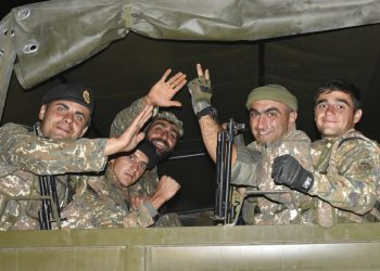 En esta imagen difundida el martes 6 de octubre de 2020, soldados armenios saludan a un fotógrafo mientras viajan en la parte trasera de un camión durante el combate con fuerzas de Azerbaiyán en la autoproclamada República de Nagorno Karabaj, el domingo 4 de octubre de 2020. Foto: Oficina de prensa del Ministerio de Defensa de Armenia, vía AP.