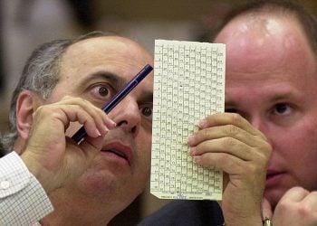 Dos abogados, uno de cada partido, certifican ocularmente la validez de una boleta en el condado de Palm Beach durante el reconteo de las elecciones presidenciales de 2000. Foto: Wilfredo Lee/AP/Archivo.