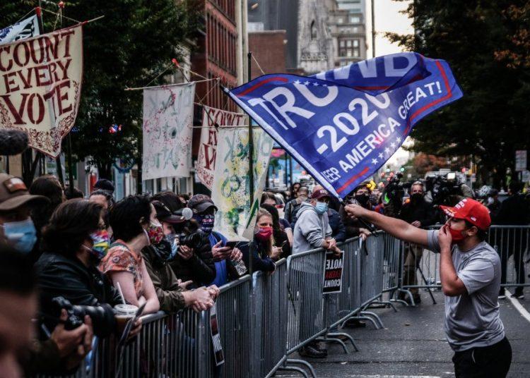 Un seguidor del presidente Trump ondea una bandera frente a un grupo de seguidores de Joe Biden en el exterior de un centro de escrutinio electoral en Filadelfia. Foto: Mario Cruz / EFE