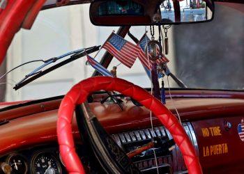 Vista del interior de un automóvil clásico de fabricación norteamericana, adornado con banderas de Cuba y Estados Unidos en La Habana. Foto: Ernesto Mastrascusa / EFE/Archivo.