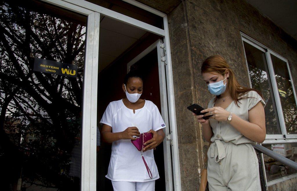 Una trabajadora de salud cubana deja una oficina de Western Union después de cobrar dinero mientras otra clienta espera su turno el último día de trabajo de la oficina en La Habana, Cuba, el lunes 23 de noviembre de 2020. Foto: AP/Ismael Francisco.