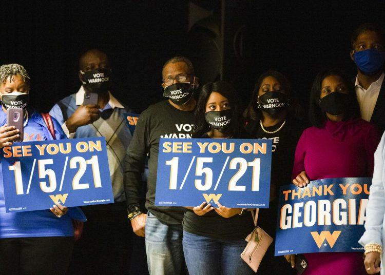 Partidarios del reverendo Raphael Warnock sostienen carteles alusivos a la segunda vuelta para el Senado. Foto: Vox.