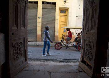 Unas personas pasan frente a unas puertas exteriores en La Habana. Foto: Otmaro Rodríguez.