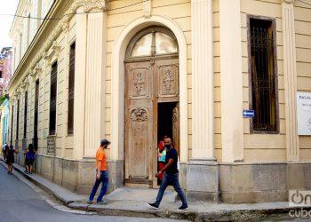 Unas personas pasan frente a una puerta exterior en La Habana. Foto: Otmaro Rodríguez.