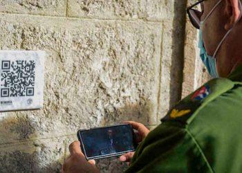 """El presidente del Consejo de Defensa Provincial de La Habana, Luis Antonio Torres Iríbar, observa un video del desaparecido historiador Eusebio Leal tras escanear un código Qr colocado en el Palacio del Segundo Cabo, durante la inauguración del proyecto """"Memoria de las piedras"""", en la capital cubana. Foto: Agencia Cubana de Noticias."""