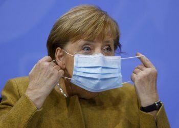 La canciller alemana Angela Merkel se retira la mascarilla el miércoles 25 de noviembre de 2020 antes de una conferencia de prensa. Foto: Odd Andersen/Pool Foto vía AP.