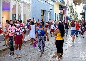 Personas con mascarillas en la calle Obispo de La Habana, entre ellas estudiantes de la enseñanza primaria, tras el reinicio del curso escolar en la capital cubana. Foto: Otmaro Rodríguez.