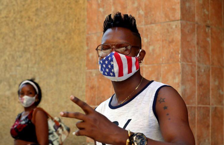 Un joven usa una mascarilla con diseño de la bandera de Estados Unidos, mientras posa para una foto en La Habana. Foto: Ernesto Mastrascusa / EFE.