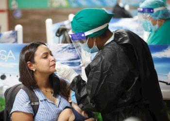 Una trabajadora sanitaria toma una muestra para un test de PCR, para detectar el coronavirus SARS CoV-2, en el aeropuerto de La Habana tras el reinicio de sus operaciones regulares el 15 de noviembre de 2020. Foto: Yander Zamora / EFE.