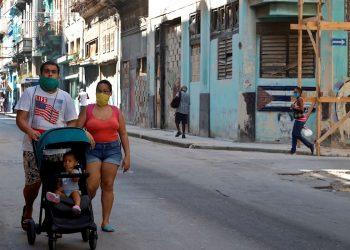 Una pareja pasea a su hijo en La Habana. Foto: Ernesto Mastrascusa / EFE.