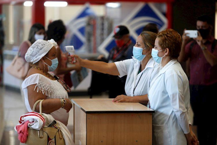 Trabajadoras del aeropuerto de La Habana toman la temperatura a una viajera tras el reinicio de las operaciones regulares, suspendidas desde hace meses a causa de la pandemia. Foto: Yander Zamora / EFE.