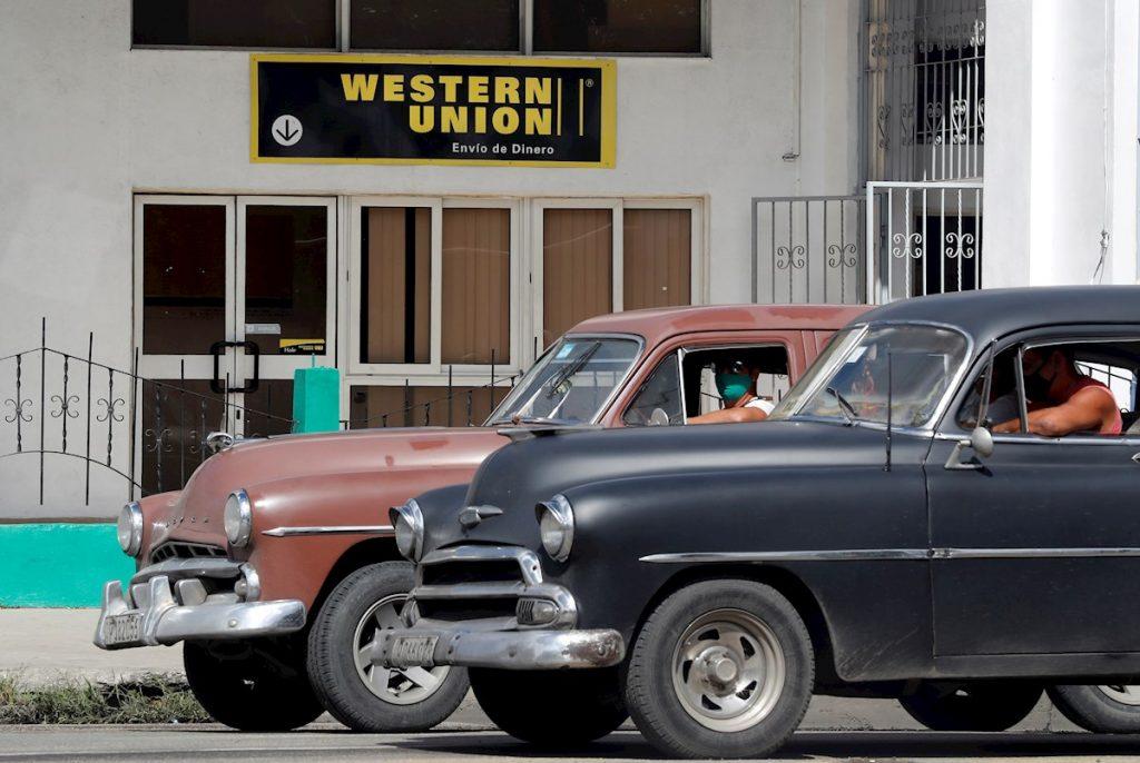 Dos autos antiguos pasan frente a una oficina de Western Unión, en La Habana, en su último día de operaciones en Cuba, el 23 de noviembre de 2020. Foto: Ernesto Mastrascusa / EFE.