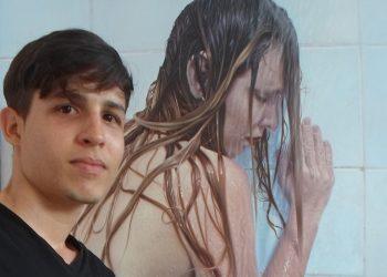 """El joven artista cubano Yoandry Cáceres Rivero junto a su obra """"Violencia No"""", premiada en España. Foto: Perfil de Facebook del artista."""