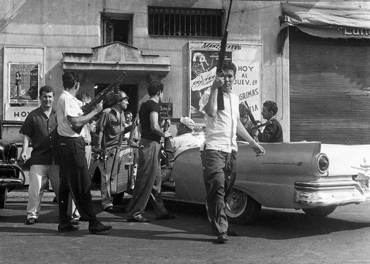 Grupo de personas disparando-desde-el-costado-del-cine-Mazanares al-edificio-de-Carlos-III-e-infanta, el 1ero de enero de 1959. Foto: Ernesto Fernández.
