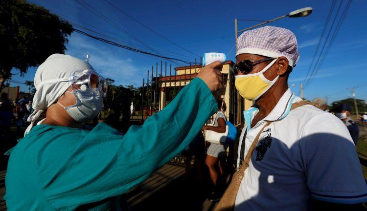 Una trabajadora de la salud le toma la temperatura a un religioso en su visita a la iglesia de El Rincón, donde se le rinde tributo a San Lázaro, el 17 de diciembre de 2020 en La Habana. Foto: Ernesto Mastrascusa / EFE.