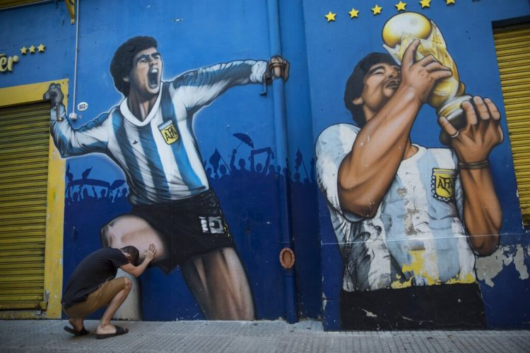 Augusto Canosa reza al tocar una pintura de Diego Maradona cerca del estadio La Bombonera de Boca Juniors en Buenos Aires, Argentina, el viernes 27 de noviembre de 2020. Foto: AP/Rodrigo Abd.