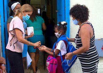 Una educadora aplica un desinfectante en las manos de una niña a la entrada de su escuela en La Habana. Foto: Otmaro Rodríguez.