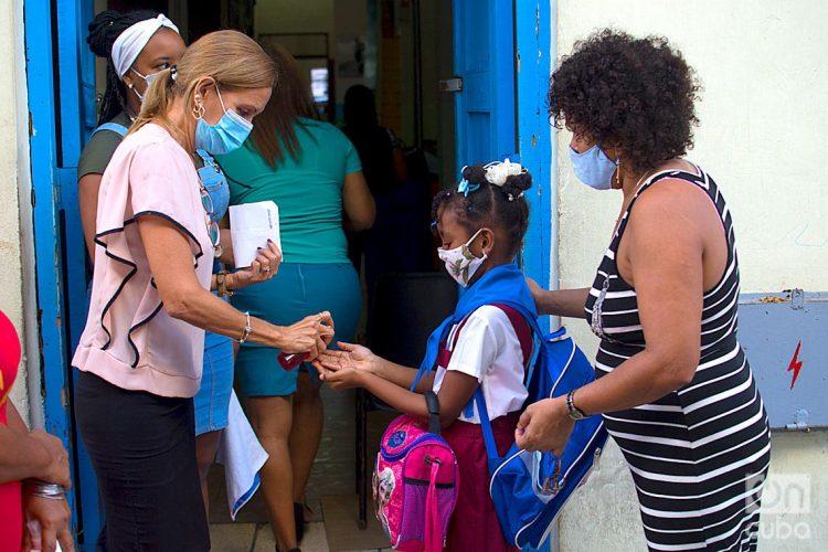 Una educadora aplica un desinfectante en las manos de una niña a la entrada de su escuela en La Habana. Foto: Otmaro Rodríguez / Archivo OnCuba.