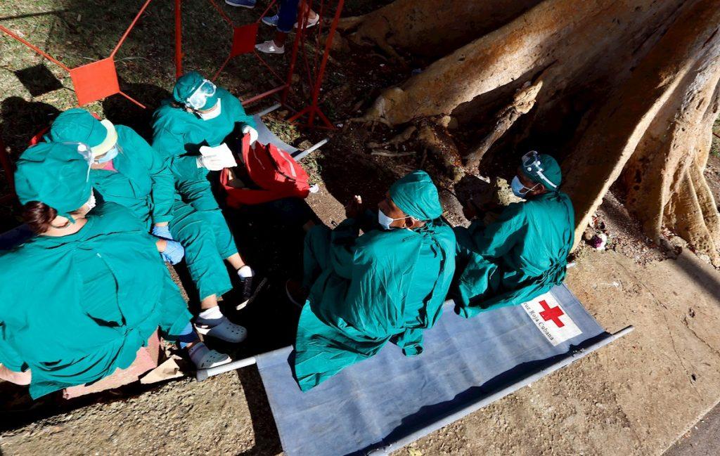 Trabajadores de la salud descansan tras la visita de religiosos al Santuario del Rincón, donde se le rinde tributo a San Lázaro. Foto: Ernesto Mastracusa / EFE.