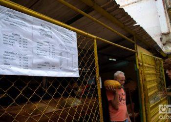 """Un hombre sale con sus compras de un mercado agropecuario en La Habana. En primer plano, el listado de precios """"topados"""" por el gobierno, el 1 de diciembre de 2020. Foto: Otmaro Rodríguez."""
