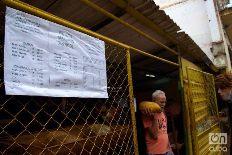 """Un hombre sale con sus compras de un mercado agropecuario en La Habana. En primer plano, el listado de precios """"topados"""" por el gobierno. Foto: Otmaro Rodríguez/Archivo OnCuba."""