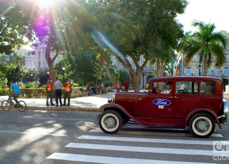 Un auto clásico pasa frente a un grupo de policías en el Parque Central de La Habana, el 1 de diciembre de 2020. Foto: Otmaro Rodríguez.