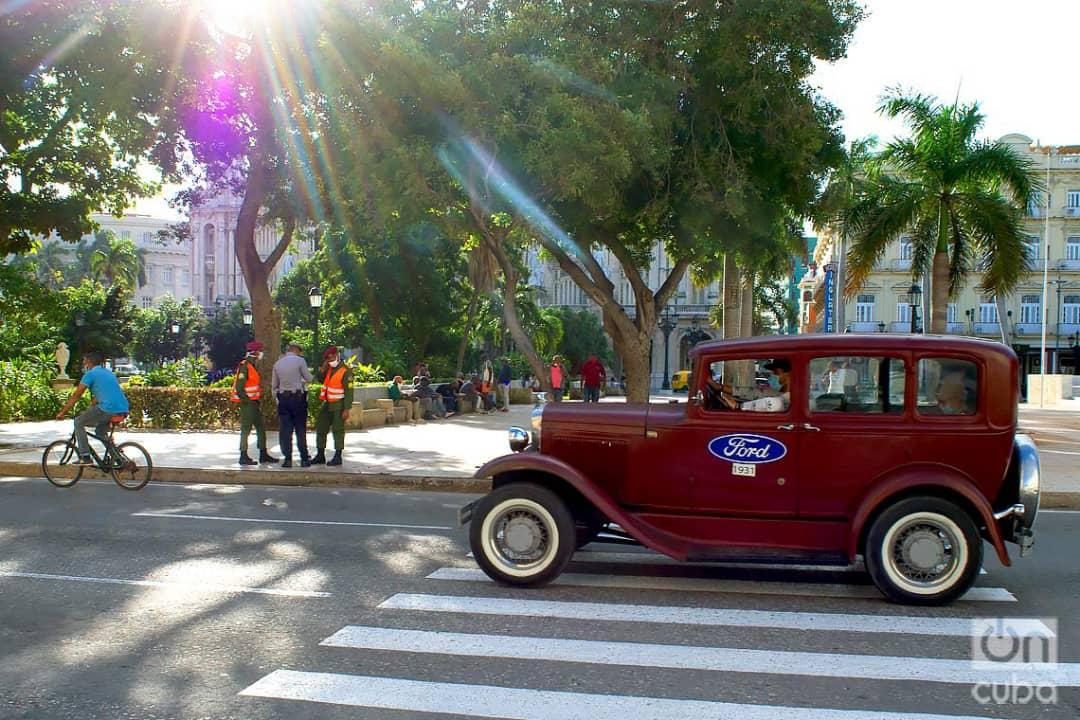 Un auto clásico pasa frente a un grupo de policías en el Parque Central de La Habana, el 2 de diciembre de 2020. Foto: Otmaro Rodríguez.