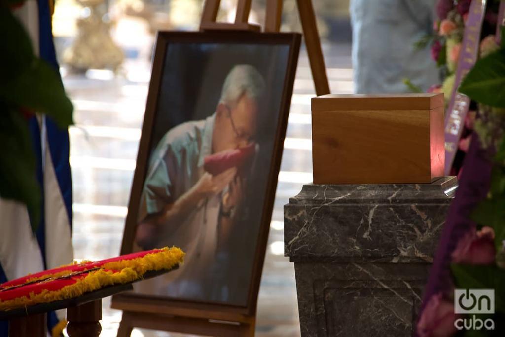 Caja con las cenizas del Historiador de La Habana y un retrato suyo en el que besa la bandera cubana, colocado para sus exequias en el Capitolio Nacional, el 17 de diciembre de 2020. Foto: Otmaro Rodríguez.