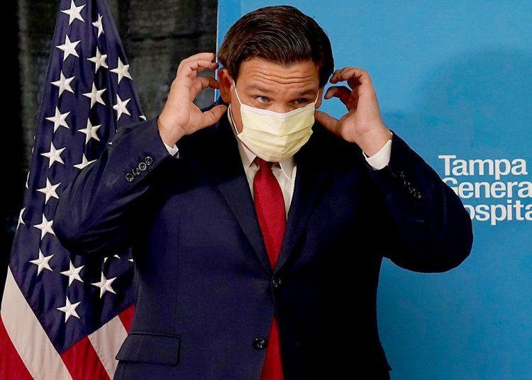 Una de las raras ocasiones en que el gobernador de Florida ha usado máscara en público, en este caso durante una visita al Hospital General de Tampa. Foto: Chris O'Meara?AP.