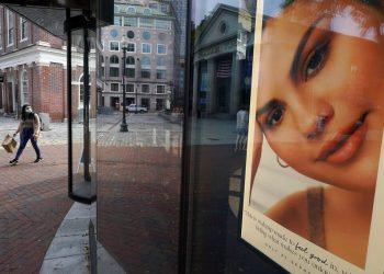Una mujer carga una bolsa de compras mientras camina frente a una tienda de cosméticos cerca de Faneuil Hall. Foto:  Steven Senne/AP.