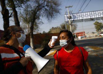 Trabajadora le toma la temperatura a una mujer con la intención de reducir la propagación del coronavirus, en las inmediaciones del mercado Central de Abastos. Foto: Rebecca Blackwell/AP.