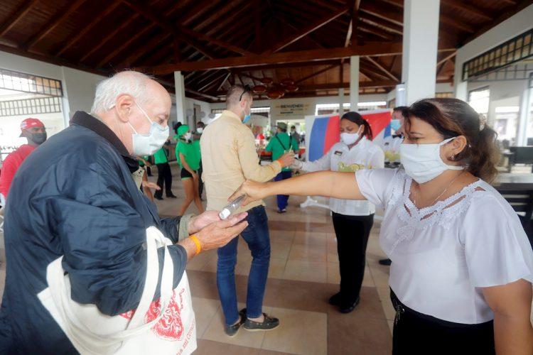 Trabajadoras del turismo ofrecen gel desinfectante a los visitantes que llegan a un hotel en Cayo Coco, Cuba, en diciembre de 2020. Foto: Ernesto Mastrascusa / EFE / Archivo.