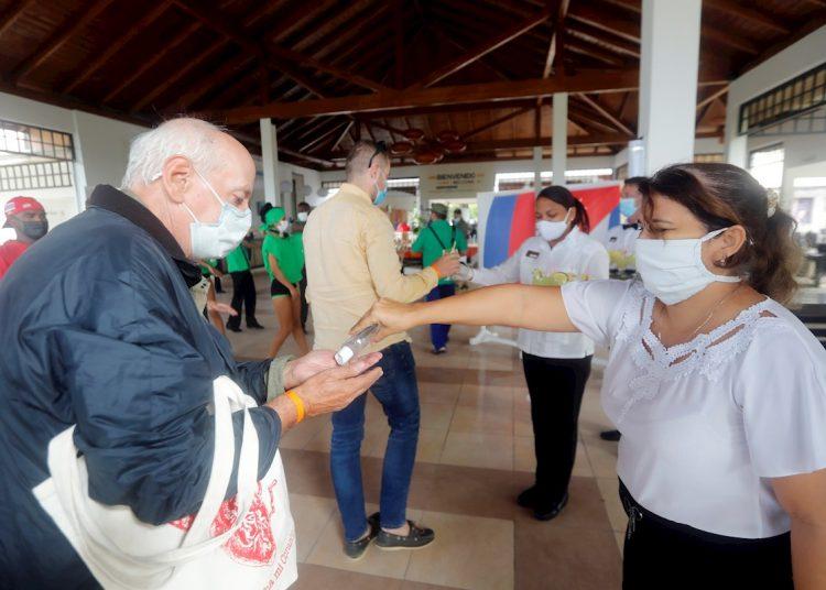 Trabajadoras ofrecen gel desinfectante a los turistas a su llegada a un hotel en Cayo Coco, en el centro de Cuba. Foto: Ernesto Mastrascusa / EFE / Archivo.