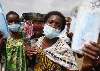 Mujeres usan y muestran mascarillas faciales donadas durante una campaña de concienciación para su empleo en Abidján, Costa de Marfil. Foto: Legnan Koula / EFE.