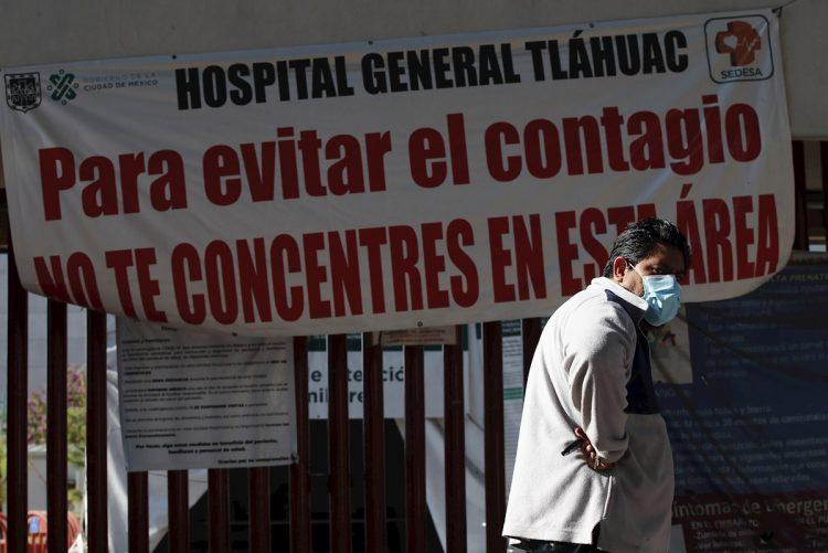 Un hombre camina frente a un letrero de advertencia de alto contagio de la COVID-19, en el Hospital General Tláhuac de Ciudad de México. Foto: José Méndez / EFE.