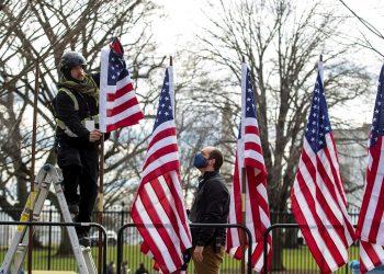 Dos trabajadores colocan banderas estadounidenses en mástiles en preparación para la inauguración en el Capitolio, el miércoles. | SHAWN THEW/EFE