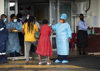 Una trabajadora de salud revisa la temperatura de una paciente en la entrada de la sala de emergencias del Hospital Académico Steve Biko, en Pretoria, Sudáfrica, el lunes 11 de enero de 2021. Foto: AP/Themba Hadebe.