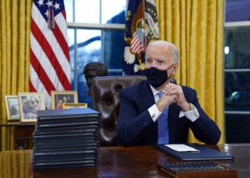 Fotografía de archivo del 20 de enero de 2021 del presidente Joe Biden esperando firmar su primera orden ejecutiva en la oficina Oval de la Casa Blanca en Washington. (AP Foto/Evan Vucci, Archivo)