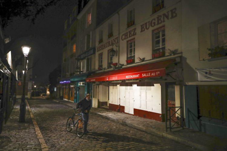 Un hombre con su bicicleta frente a varios restaurantes cerrados en Montmartre, durante el toque de queda impuesto en París por la pandemia de coronavirus. Foto: Michel Euler/AP.
