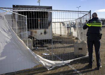 Un policía enbel pueblo pesquero holandés de Urk, el domingo 24 de enero de 2021. El puesto fue incendiado durante unos disturbios durante la primera noche de un toque de queda nacional. Foto: Peter Dejong/AP.
