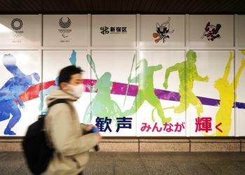 Un hombre con mascarilla pasa frente al edificio de oficinas municipales de Shinjuku, en el que se promocionan los Juegos Olímpicos reprogramados para mediados de este año, en Tokio, el viernes 29 de enero de 2021. Foto: AP/Hiro Komae.