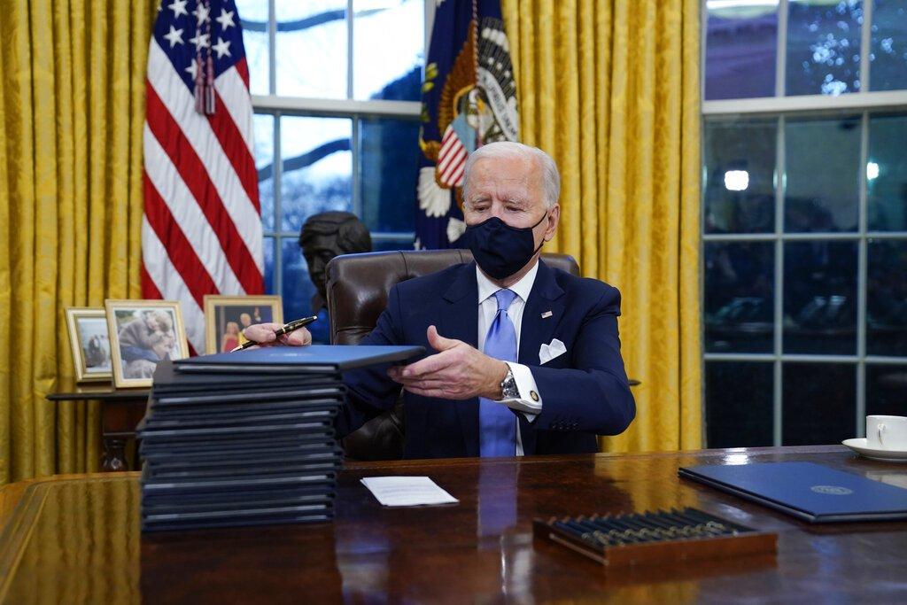 El presidente Joe Biden firma sus primeras órdenes ejecutivas, 20 de enero de 2021 en la Oficina Oval de la Casa Blanca, en Washington. Foto: AP /Evan Vucci.