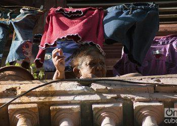 Una anciana se asoma al balcón durante el rebrote de la COVID-19 en La Habana, en enero de 2021. Foto: Otmaro Rodríguez.