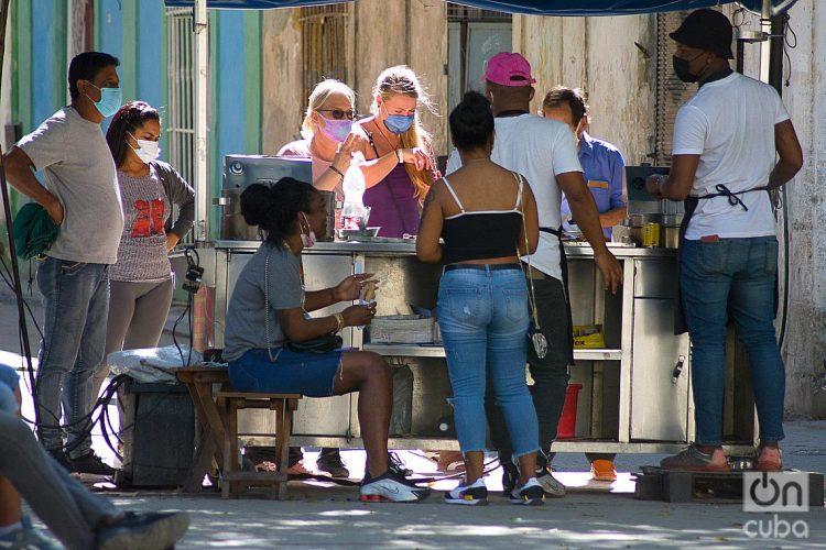 Unos turistas y otras personas en un puesto de venta de churros durante el rebrote de la COVID-19 en La Habana, en enero de 2021. Foto: Otmaro Rodríguez.