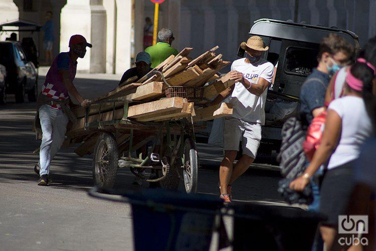 Hombres transportando madera durante el rebrote de la COVID-19 en La Habana, en enero de 2021. Foto: Otmaro Rodríguez.