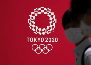 Fotografía de archivo de personas con tapabocas pasando frente a un cartel con la imagen de los Juegos Olímpicos Tokio 2020 el 15 de julio de 2020 en Tokio (Japón). Foto: EFE/Kimimasa Mayama.